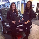 Two staff at a motor dealership collecting prospects data