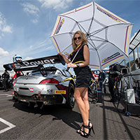 Sexy grid girl next to supercar on grid of motorsport track