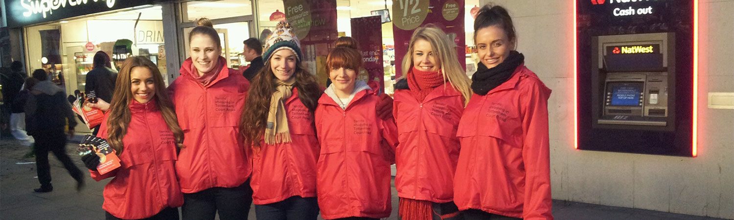 Line of promotional models ready to hand out leaflets to promote shopping centre